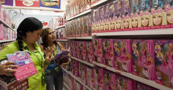 Shoppers look at the selection of Barbie dolls for sale at a store in Caracas, Venezuela, Monday, Nov. 10, 2014. (Ariana Cubillos/AP)